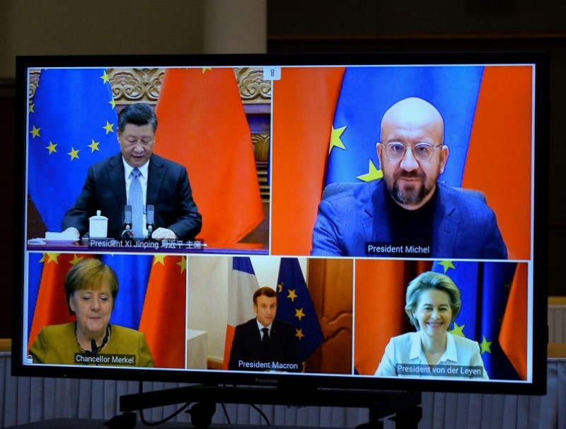 European Commission President Ursula von der Leyen, European Council President Charles Michel, German Chancellor Angela Merkel, French President Emmanuel Macron and Chinese President Xi Jinping are seen on a screen during a video conference, in Brussels, Belgium, 30 December 2020. (Johanna Geron/REUTERS)