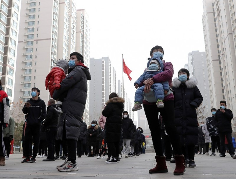 People practise social distancing as they line up for a second round of citywide nucleic acid testing at a residential compound, following new cases of the Covid-19 coronavirus in Shijiazhuang, Hebei province, China, 12 January 2021. (China Daily via Reuters)