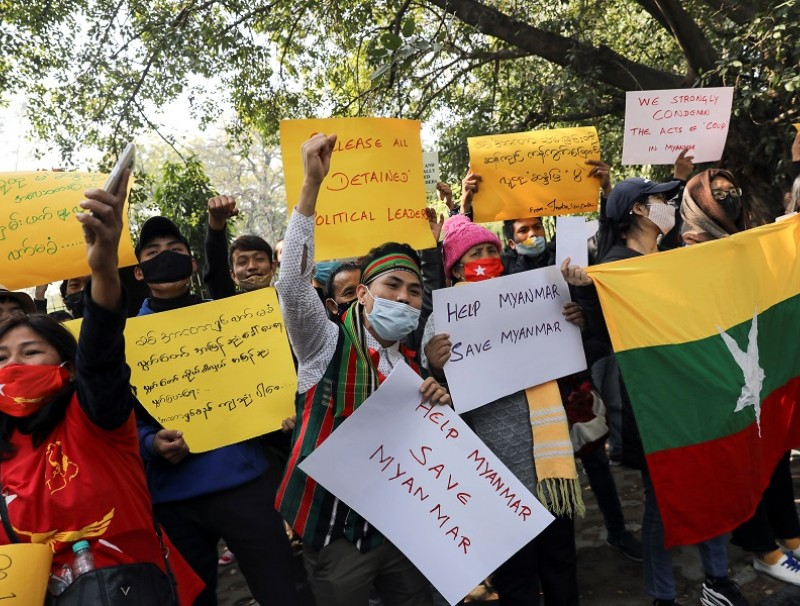 Myanmar citizens living in India hold placards and shout slogans during a protest against the military coup in Myanmar, in New Delhi, India, 5 February 2021. (Anushree Fadnavis/Reuters)