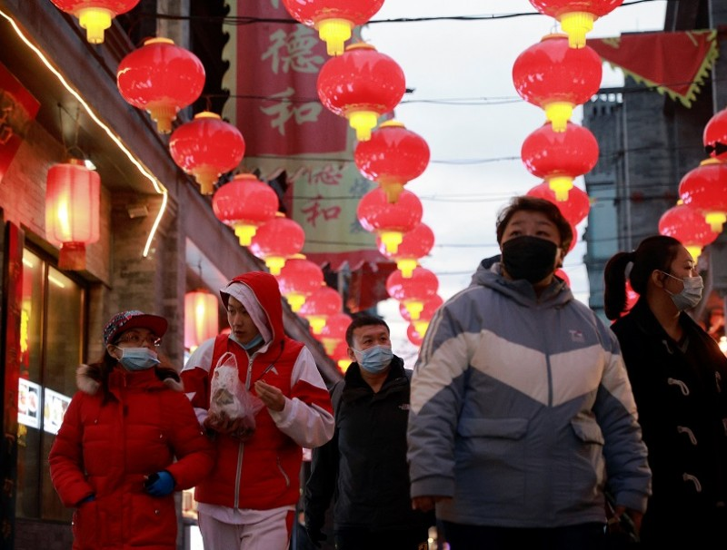 People walk in a historic street decorated for Lunar New Year celebrations in Beijing, China, 8 February 2021. (Thomas Peter/Reuters)