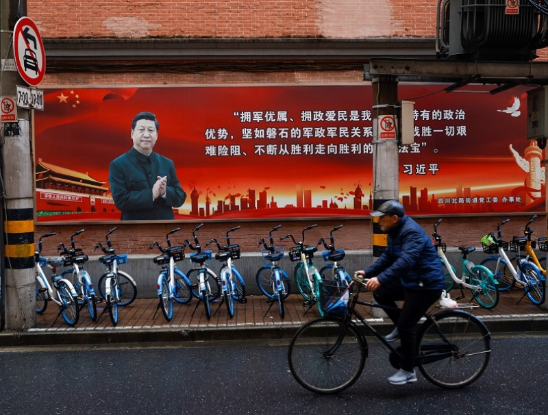 A picture of Chinese President Xi Jinping overlook a street ahead of the National People's Congress (NPC), in Shanghai, China, 1 March 2021. (Aly Song/Reuters)