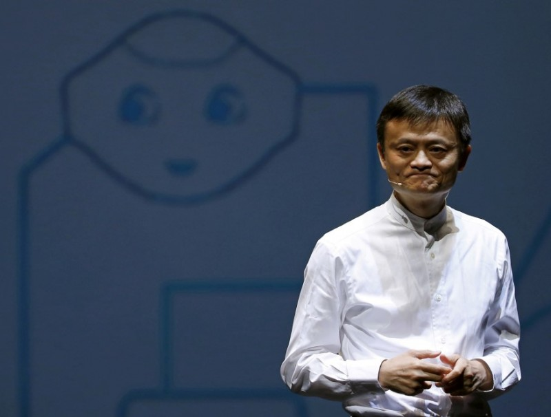 Jack Ma, founder and executive chairman of China's Alibaba Group, speaks in front of a picture of SoftBank's human-like robot named 'Pepper' during a news conference in Chiba, Japan, 18 June 2015. (Yuya Shino/Reuters)