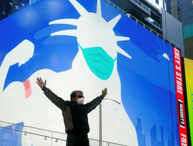 A man poses for a photo on the Red Steps in Times Square as an image of the Statue of Liberty wearing a mask is projected on a billboard amid the Covid-19 pandemic in the Manhattan borough of New York City, New York, US on 20 April 2021. (Carlo Allegri/Reuters)