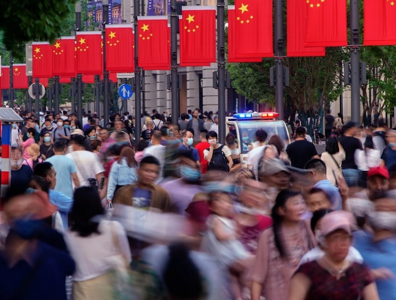 People walk along Nanjing Road, a main shopping area in Shanghai, China, 10 May 2021. (Aly Song/Reuters)