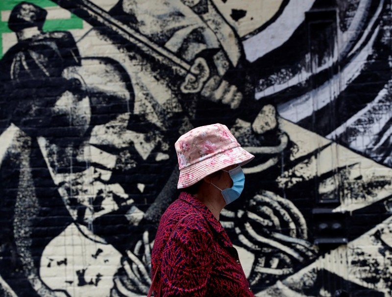 A woman wearing a protective face mask walks by a mural in Manhattan's Chinatown district of New York City, US, 2 June 2021. (Shannon Stapleton/Reuters)