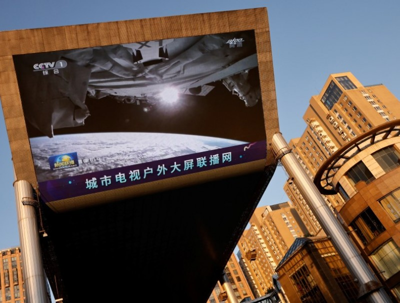 A giant screen shows a view of earth from the Tianhe core module of China's space station, at a shopping mall in Beijing, China, 18 June 2021. (Thomas Peter/Reuters)