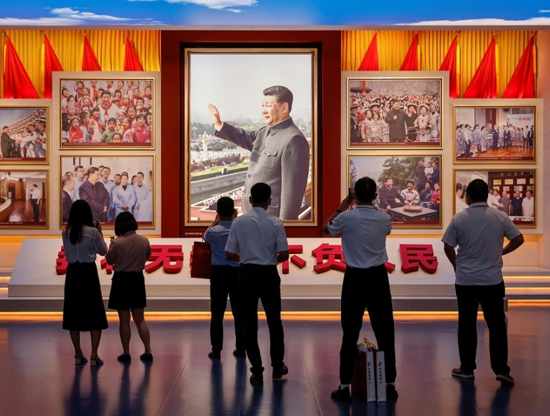 People look at images showing Chinese President Xi Jinping at the Museum of the Communist Party of China that was opened ahead of the 100th founding anniversary of the Party in Beijing, China, 25 June 2021. (Thomas Peter/Reuters)