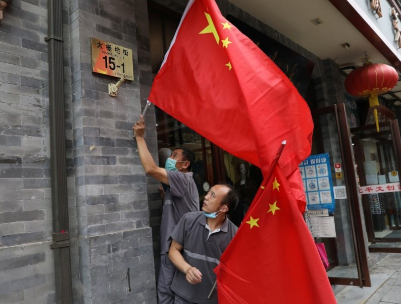 Workers set Chinese national flags on a shopping street ,ahead of a rehearsal for the celebrations to mark the 100th founding anniversary of the Communist Party of China, in Beijing, China, 26 June 2021. (Tingshu Wang/Reuters)