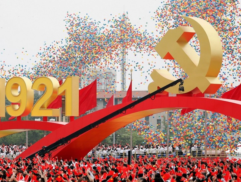Participants wave national and party flags as balloons are released at the end of the event marking the 100th founding anniversary of the Communist Party of China, at Tiananmen Square in Beijing, China, 1 July 2021. (Carlos Garcia Rawlins/Reuters)