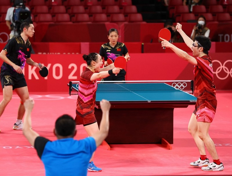 Mima Ito and Jun Mizutani of Japan celebrate winning their match against Xu Xin and Liu Shiwen of China, Tokyo Olympics, 26 July 2021. (Thomas Peter/Reuters)
