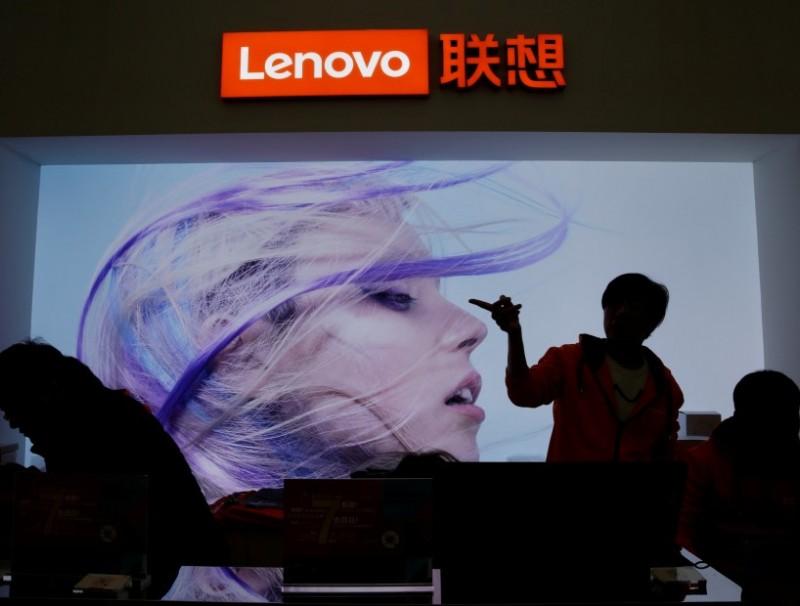 An employee gestures next to a Lenovo logo at Lenovo Tech World in Beijing, China, 15 November 2019. (Jason Lee/Reuters)