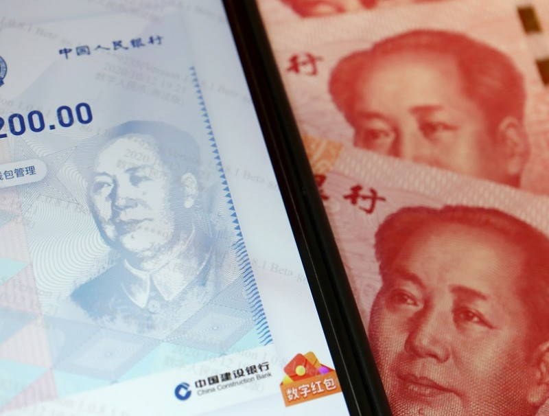 China's official app for digital yuan is seen on a mobile phone next to 100 RMB banknotes in this illustration picture taken on 16 October 2020. (Florence Lo/Illustration/File Photo/Reuters)