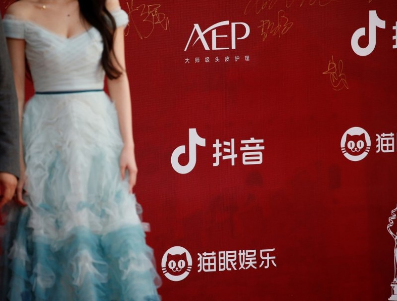 Actors stand near a board with logos of Maoyan Entertainment and Chinese company ByteDance's app TikTok, known locally as Douyin, at a red carpet ceremony at the Beijing International Film Festival, in Beijing, China, 20 September 2021. (Tingshu Wang/Reuters)