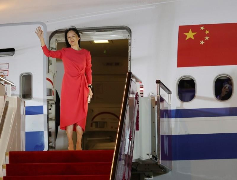 Huawei Chief Financial Officer Meng Wanzhou waves as she steps out of a charter plane at Shenzhen Bao'an International Airport in Shenzhen, Guangdong Province, China, 25 September 2021. (Jin Liwang/Xinhua via Reuters)