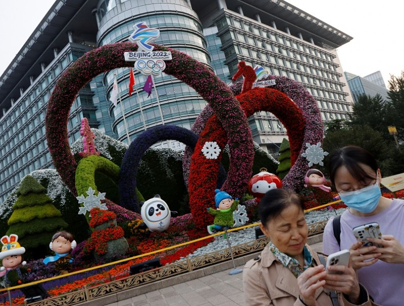 People check their phones near a Beijing 2022 Winter Olympics-themed floral installation set up ahead of the Chinese National Day, in Beijing, China, 30 September 2021. (Florence Lo/Reuters)