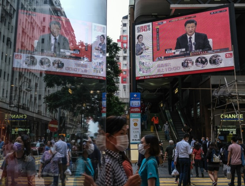 A news report on Chinese President Xi Jinping's speech in the city of Shenzhen is shown on a public screen in Hong Kong, 14 October 2020. (Roy Liu/Bloomberg)