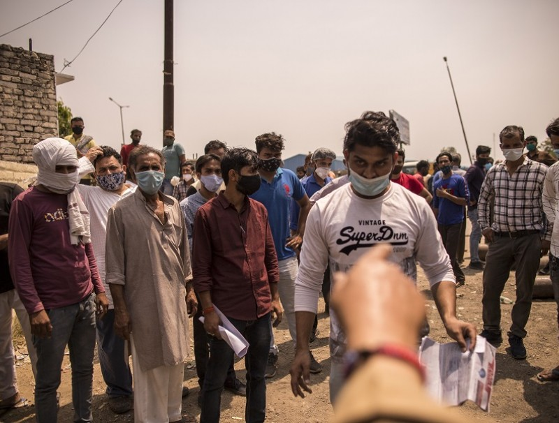 A man is called forward while waiting in line at a medical oxygen refilling facility in Moradabad, Uttar Pradesh, India on 4 May 2021. (Anindito Mukherjee/Bloomberg)