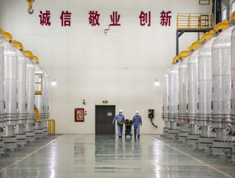 Employees walk past chemical vapour deposition chambers at the Daqo New Energy Corp. plant in Shihezi, Xinjiang province, China, 11 May 2021. (Qilai Shen/Bloomberg)