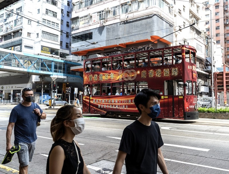 Pedestrians walk past a tram featuring an advertisement celebrating the centenary of the Chinese Community Party and the anniversary of Hong Kong's return to Chinese rule in Hong Kong, China on 1 July 2021. (Chan Long Hei/Bloomberg)