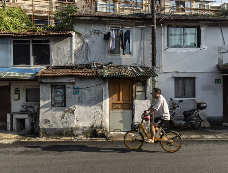 A commuter rides his bicycle through an older neighborhood in Shanghai, China, on 30 August 2021. (Qilai Shen/Bloomberg)