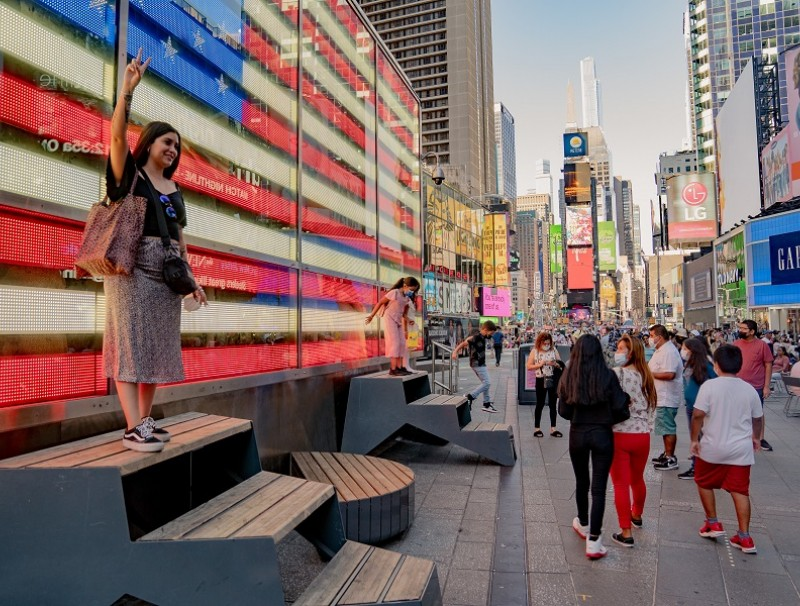 A visitor takes a photograph in front of an electronic American flag in the Times Square neighborhood of New York, US, on 4 September 2021. (Amir Hamja/Bloomberg)