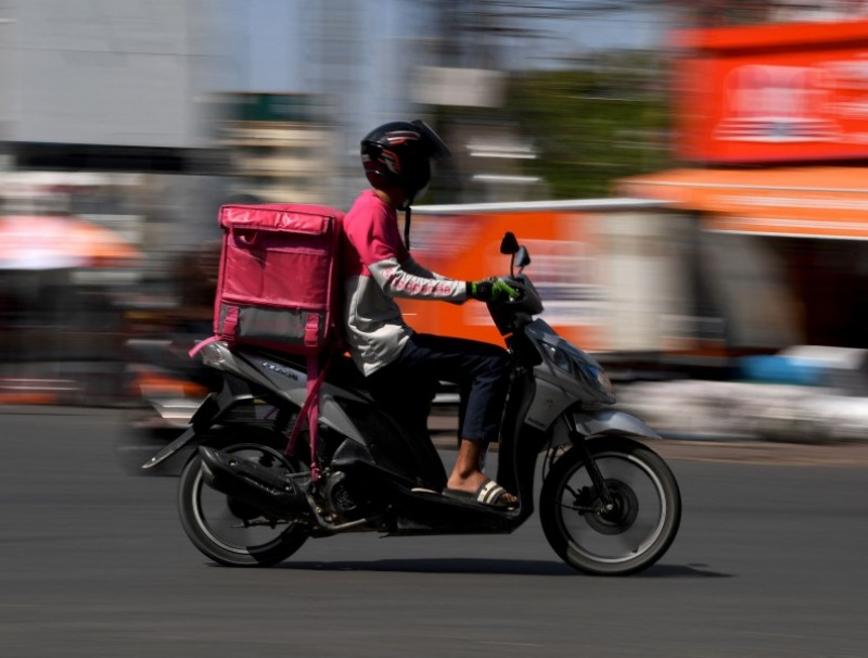 A food delivery motorist rides on a street as deliveries rise due to lockdown restrictions introduced to try to halt a surge in cases of the Covid-19 coronavirus in Phnom Penh on 26 April 2021. (Tang Chhin Sothy/AFP)