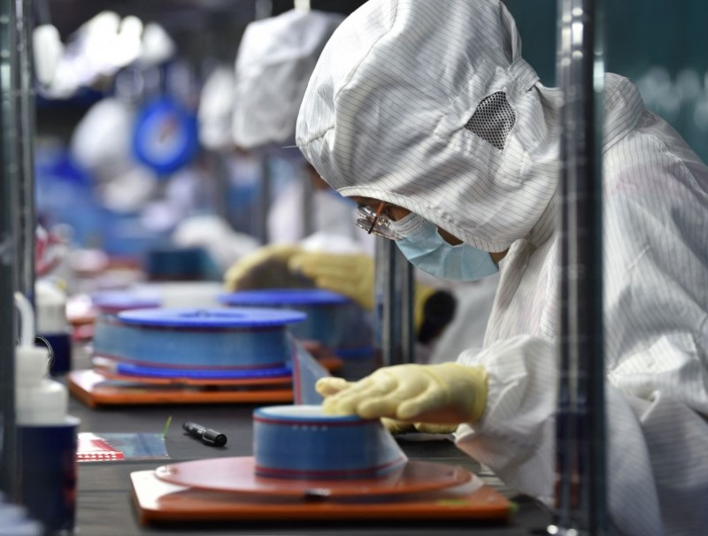 Workers produce adhesive tapes for flexible printed circuits (FPC) at a factory in Yancheng, Jiangsu province, China, on 15 September 2021. (STR/AFP)