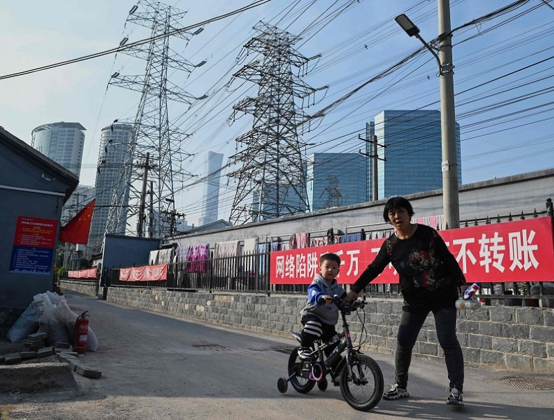 A woman guides a boy learning to cycle below power lines in Beijing, China, on 13 October 2021. (Noel Celis/AFP)