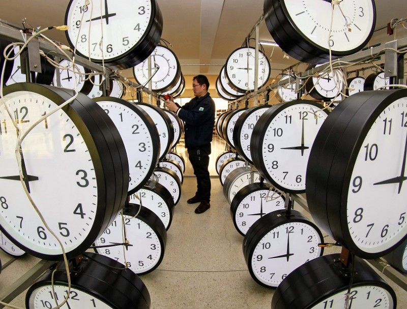 A technician checks hanging clocks at a workshop of a clock company in Yantai, Shandong province, China, on 15 December 2020. (STR/AFP)