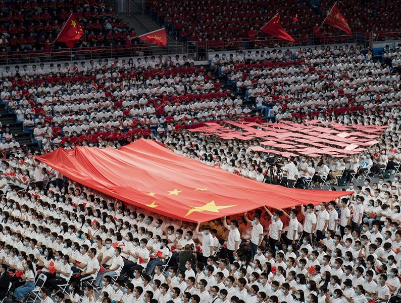 This photo taken on 26 September 2020 shows first-year students holding a Chinese flag during a commencement ceremony at Wuhan University in Wuhan, Hubei, China. (STR/AFP)