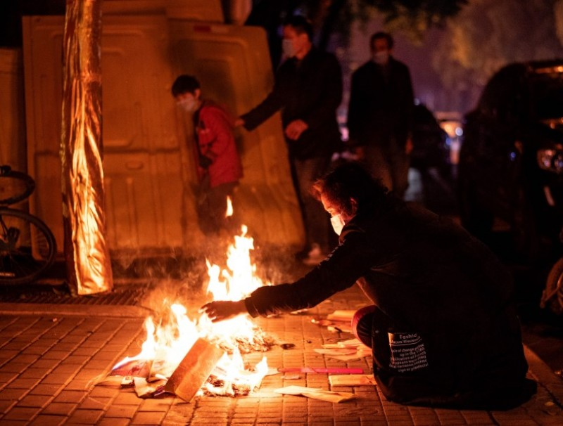 Residents burn paper offerings during the annual Qingming Festival in Wuhan, April 4, 2020. (Noel Celis/AFP)