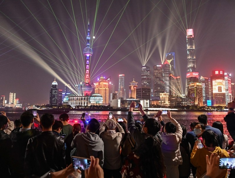 People wearing face masks on the Bund along the Huangpu River look at the light show seen in the Lujiazui financial district in Shanghai on 2 November 2020. (Hector Retamal/AFP)
