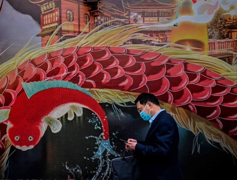 In a digital age, panic-inducing information can spread even faster than viruses. In the photograph, a man wearing a facemask as a preventive measure against Covid-19 checks his mobile phone at Yu Garden in Shanghai on 23 March 2020. (Hector Retamal/AFP)