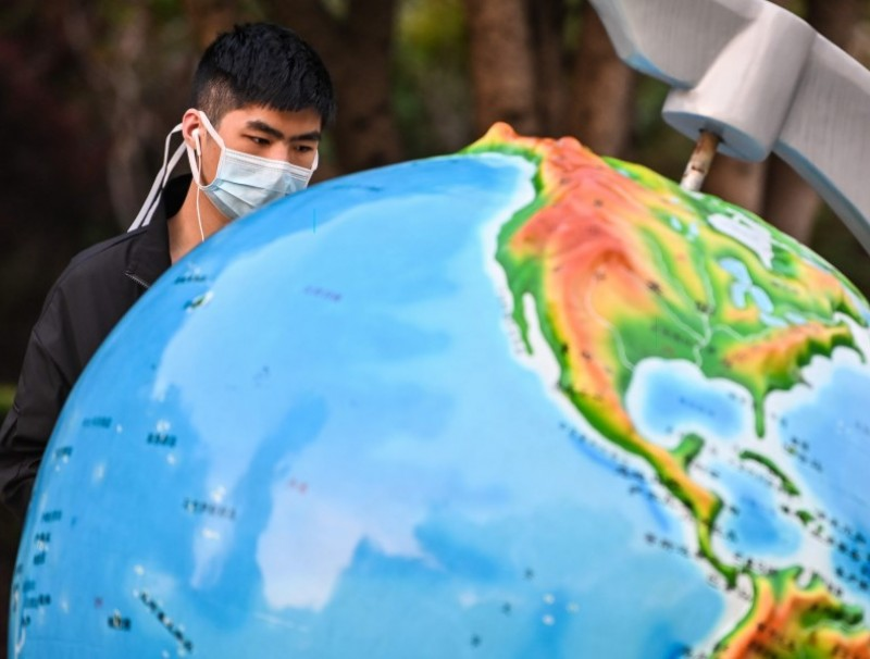 A man looks at a globe in a park in Wuhan, 8 April 2020. (Hector Retamal/AFP)