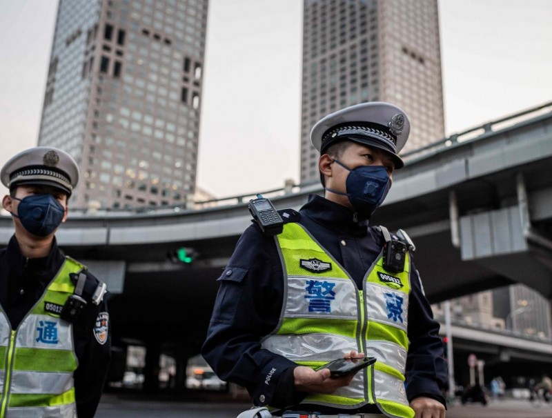 Police officers at a street crossing in Beijing, April 7, 2020. Control measures in Beijing have not been relaxed yet. (Nicolas Asfouri/AFP)