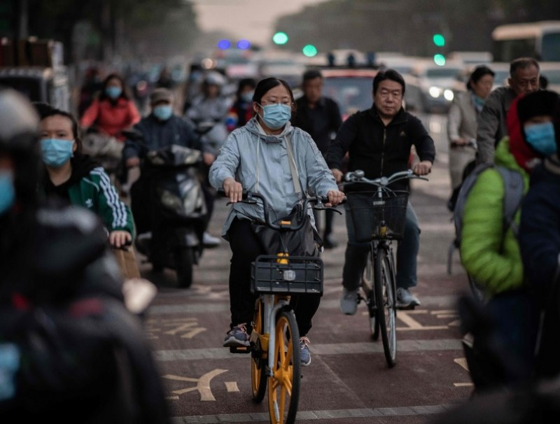 People wearing face masks as a preventive measure against the Covid-19 coronavirus commute during rush hour in Beijing on 15 October 2020. (Nicolas Asfouri/AFP)