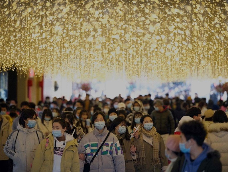 People wearing face masks walk along a shopping centre in Wuhan, Hubei province, China, on 1 January 2021. (Noel Celis/AFP)