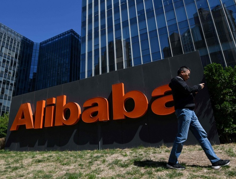 A man walks past an Alibaba sign outside the company's office in Beijing, China on 13 April 2021. (Greg Baker/AFP)