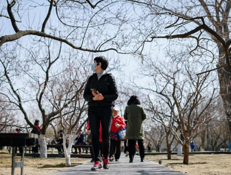 People walk in a public park under blue skies in Beijing on 16 March 2021. (Wang Zhao/AFP)