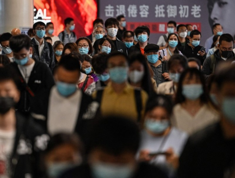People walk in a subway station in Shanghai on 12 October 2021. (Hector Retamal/AFP)
