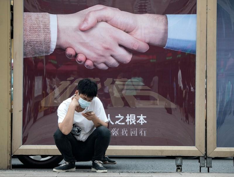 A man uses his phone outside Beijing Railway Station in Beijing on 19 August 2020. (Noel Celis/AFP)