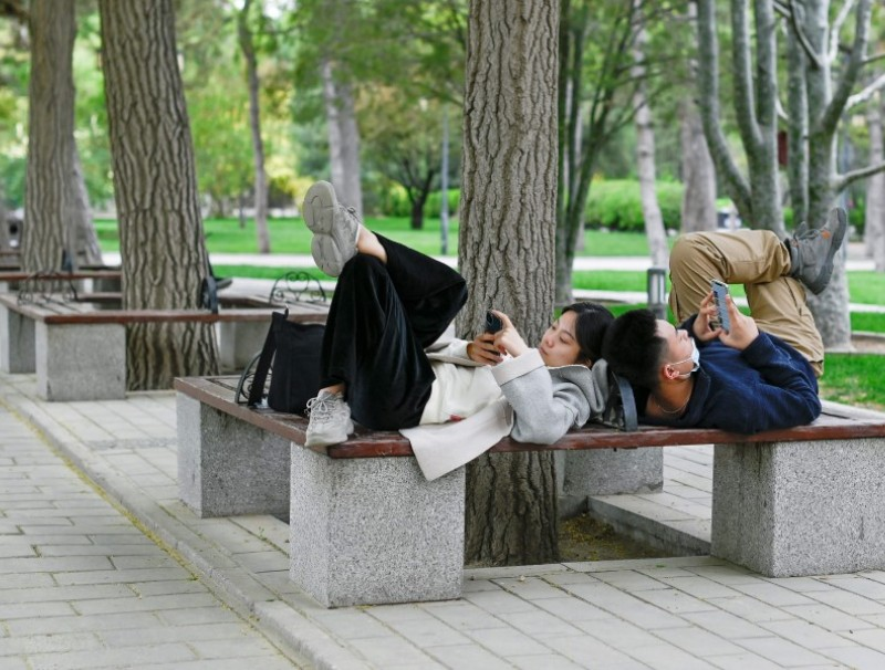 A couple use their mobile phones while sharing a bench at a park in Beijing on 21 April 2021. (Wang Zhao/AFP)
