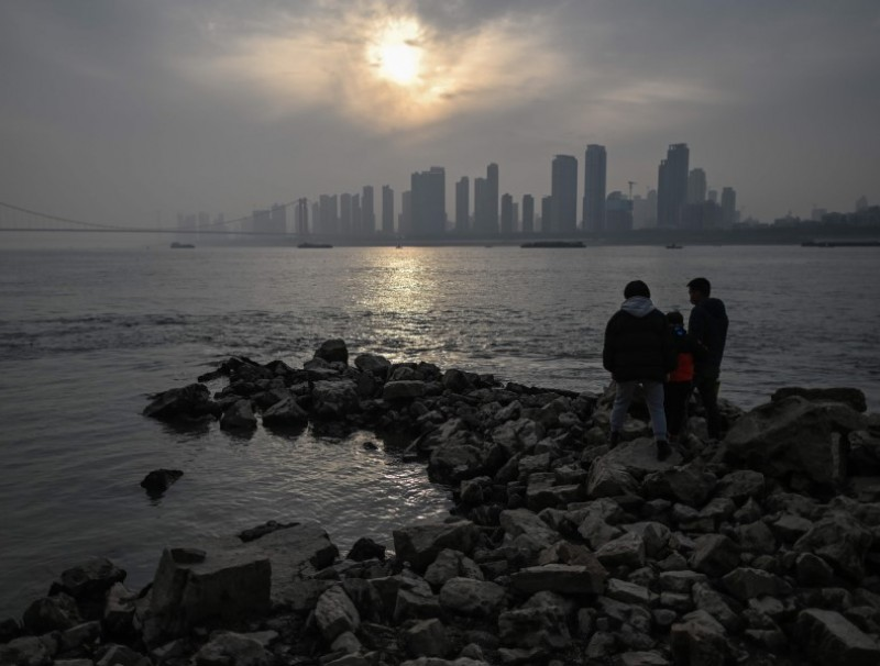 People visit the riverbank of the Yangtze River in Wuhan, China's central Hubei province on 2 February 2021. (Hector Retamal/AFP)