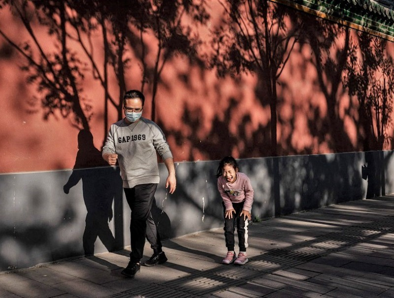 A girl reacts and laughs as she loses a game of rock-paper-scissors with her father (left) on a street outside the Forbidden City in Beijing, China on 1 May 2021. (Nicolas Asfouri/AFP)