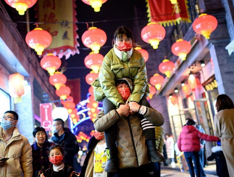 People wearing face masks walk at Qianmen street in Beijing, China, on 11 February 2021. (Noel Celis/AFP)