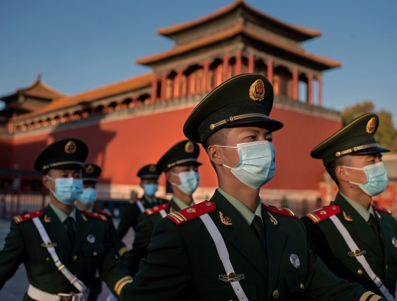 Paramilitary police officers wearing face masks march outside the Forbidden City in Beijing on 22 October 2020. (Nicolas Asfouri/AFP)