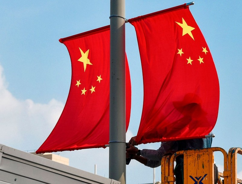 This photo taken on 24 September 2020 shows workers setting up national flags along a street ahead of the upcoming National Day in Ningbo, Zhejiang, China. (STR/AFP)