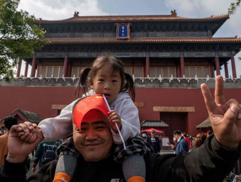 "A girl sits on the shoulders of her father outside the Forbidden City during the national day marking the 71st anniversary of the People's Republic of China and the country's national ""Golden Week"" holiday in Beijing on 1 October 2020. (Nicolas Asfouri/AFP)"