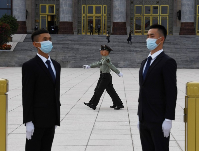 Chinese soldiers march past security guards before a reception at the Great Hall of the People on 30 September 2020. (Greg Baker/AFP)