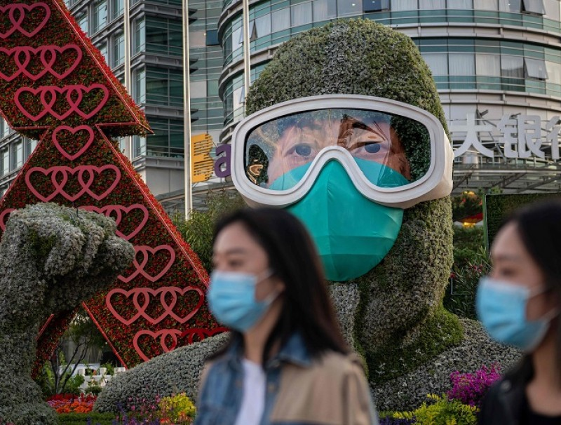 People wearing face masks walk past a flower display dedicated to frontline healthcare workers during the Covid-19 pandemic in celebration of the upcoming National Day of the People's Republic of China, in Beijing on 29 September 2020. (Nicolas Asfouri/AFP)